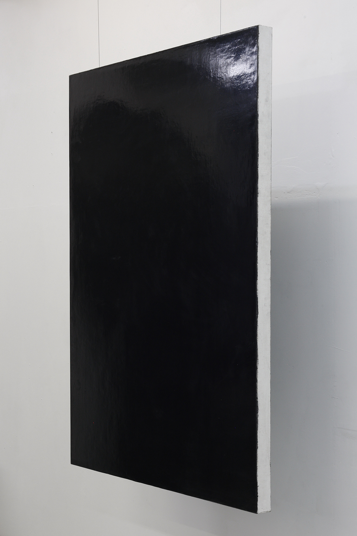 Canvas 02, black painting hanging on two steel rop with distance to the wall l Artwork by Erik Andersen