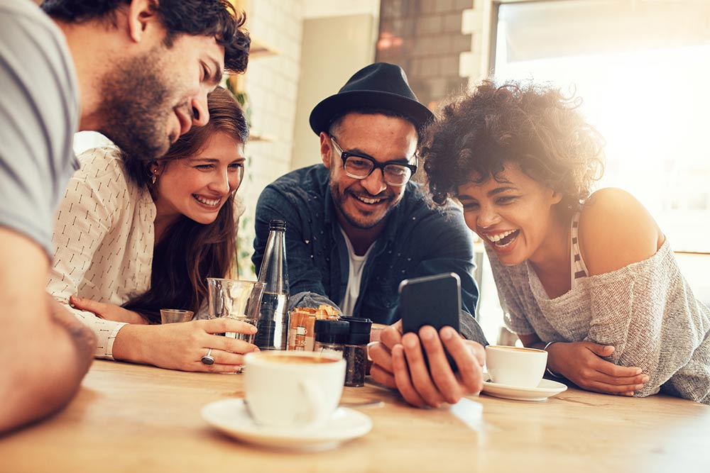 smiling people at a table watching something on a smartphone