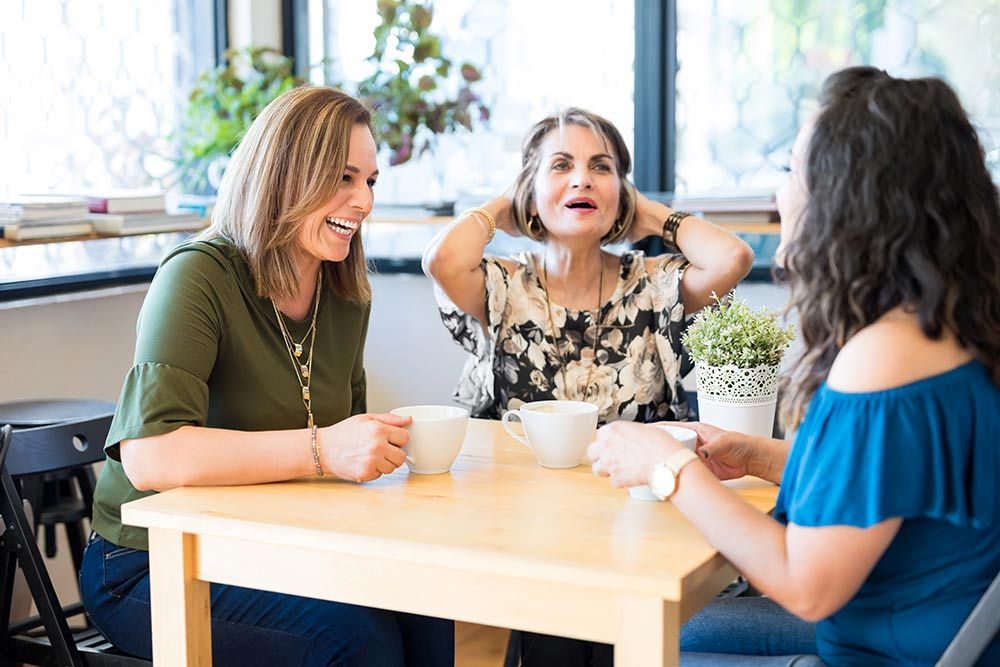 three women talking and laughing at a table