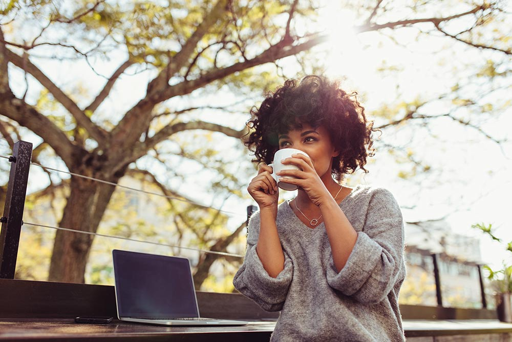 curly black woman drinking from a cup