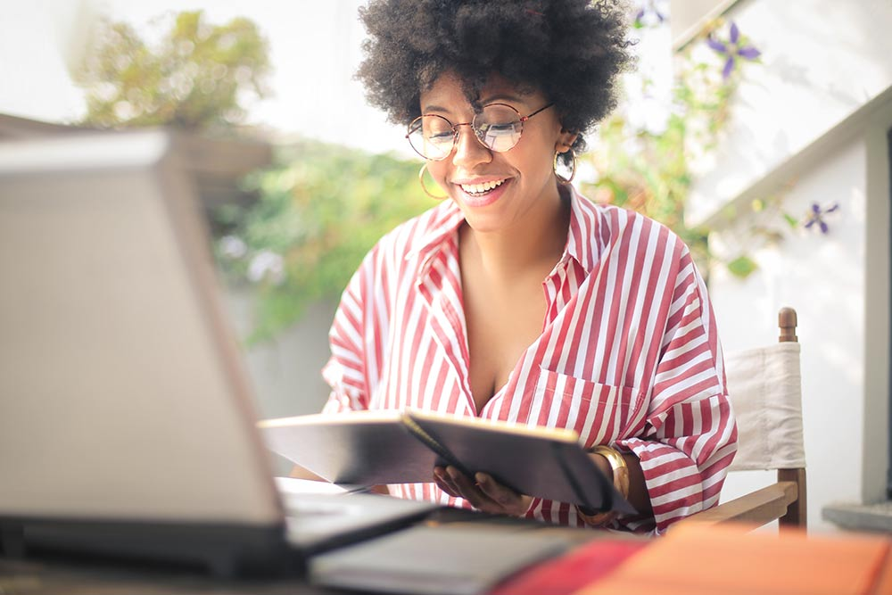 black woman smiling and reading something on a notebook