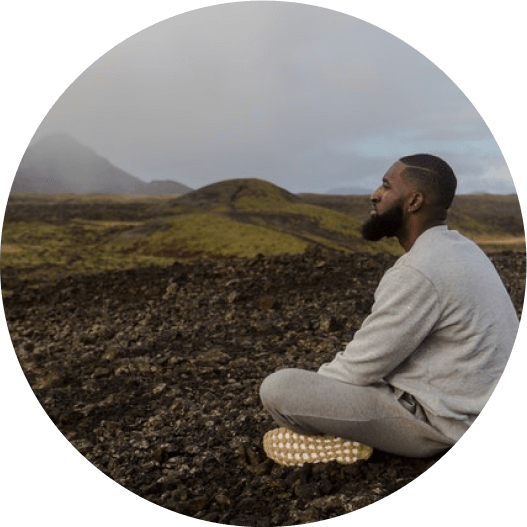Man sitting crosslegged in nature