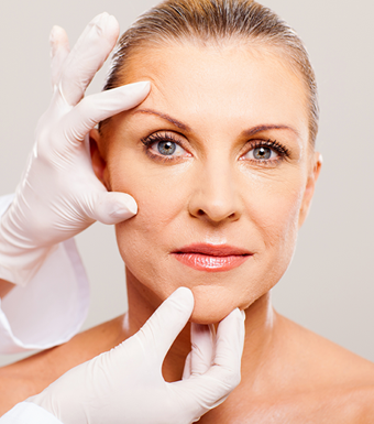 A woman's face with physician's latex gloved hands positioned at pull sites on one side of the face as compared to the other.  where areas