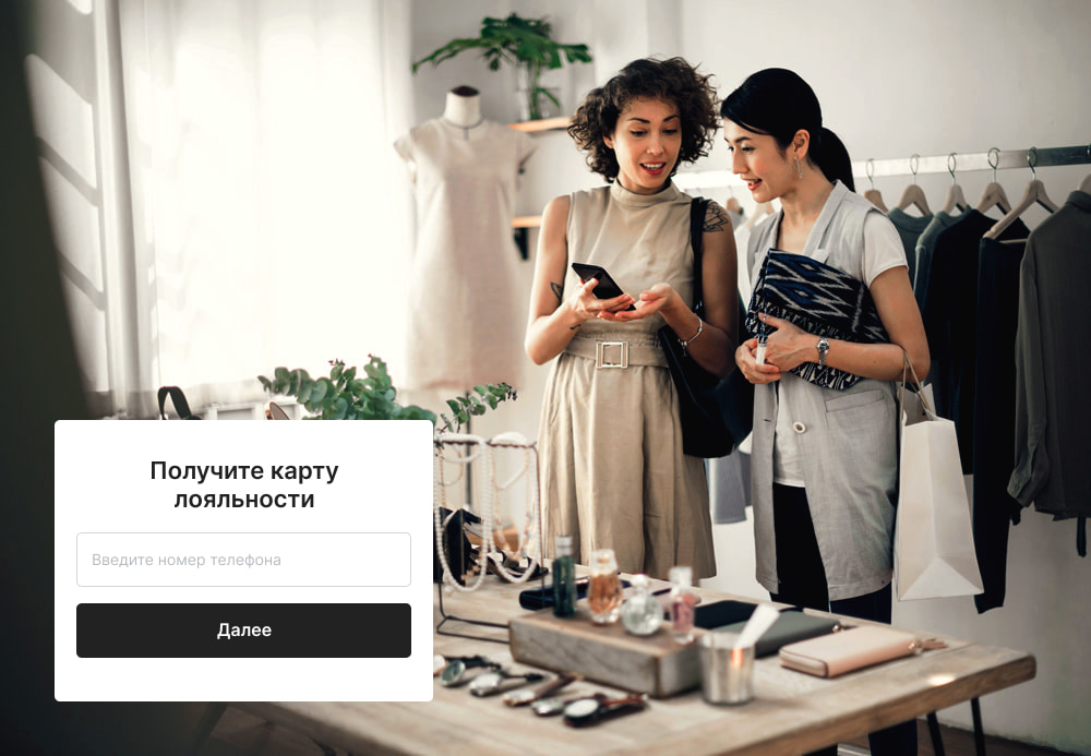 Две женщины в бутике смотрят в телефон