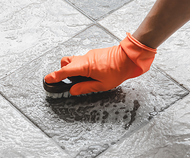 using brush to clean tiles