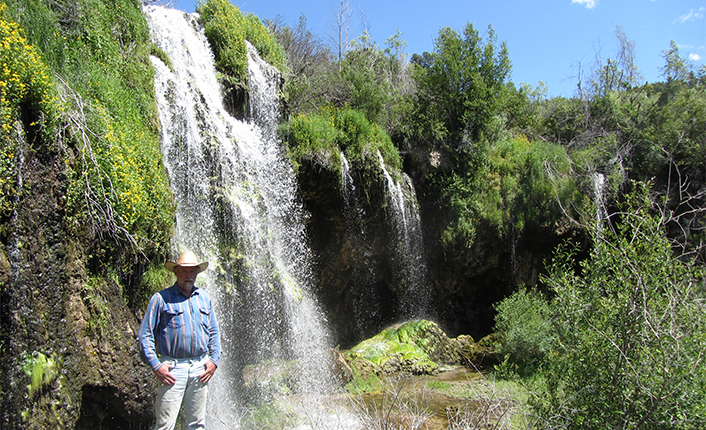 Tucked away in the hills, a spring bubbles into a large waterfall.