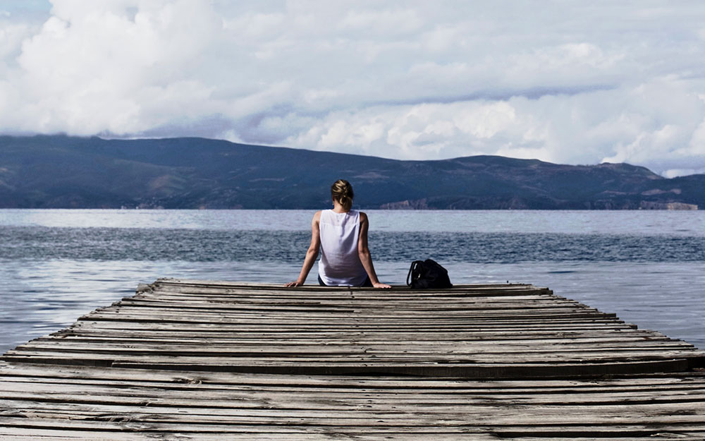 A woman sitting at the end of a pier looking onto a calm lake.