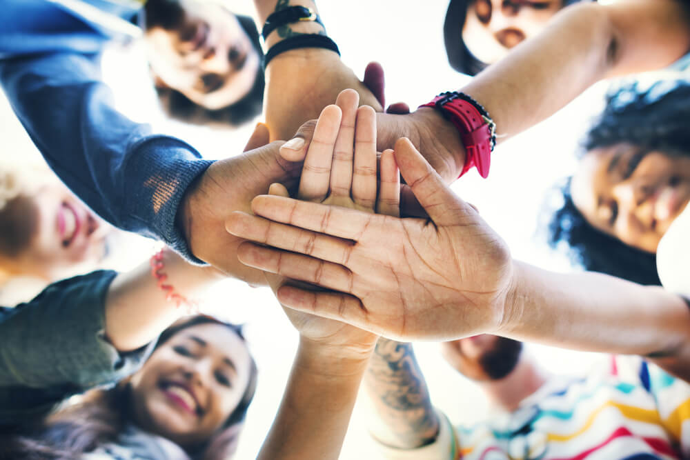 Diverse group of people stacking hands on each others