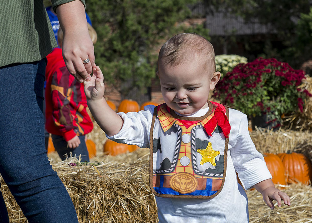 mom holding young child's hand at pumpkin fest