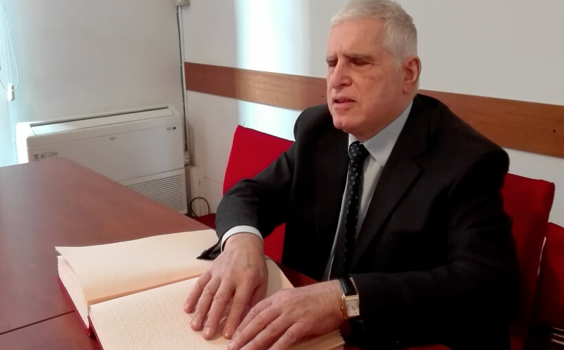 Antonio is seated wearing a suit and tie, reading a Braille text.