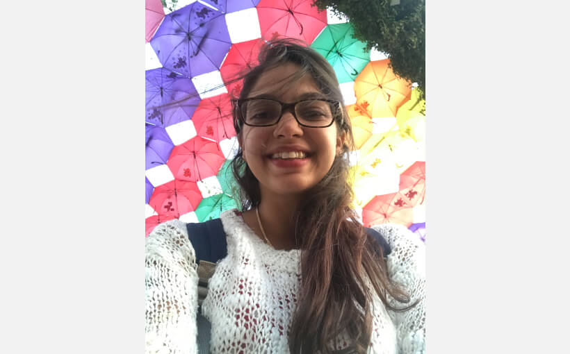 Doua wear glasses and smiles down towards the camera beneath a canopy of multicolored umbrellas.