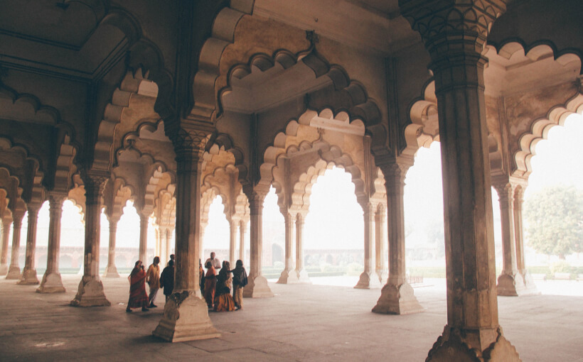A group of people wearing traditional Indian clothing standing underneath a roof with beautiful pillars and arches.