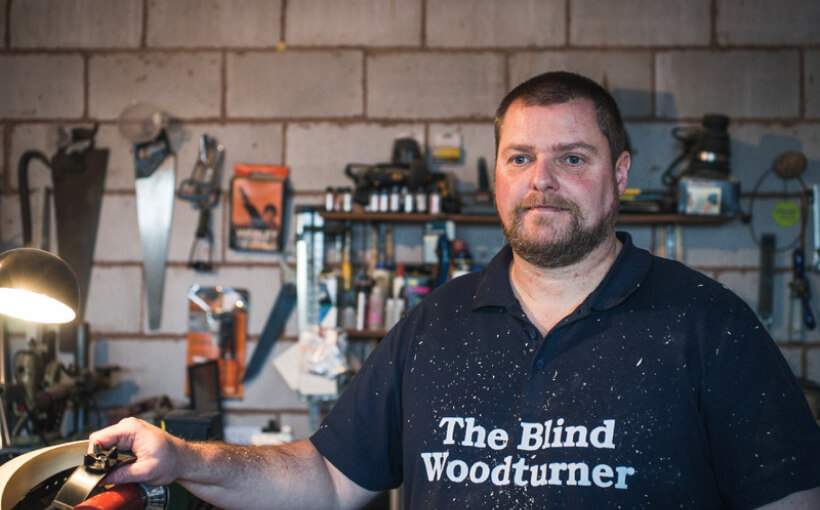 "Chris standing in his workshop wearing a t-shirt that says ""The Blind Woodturner""."