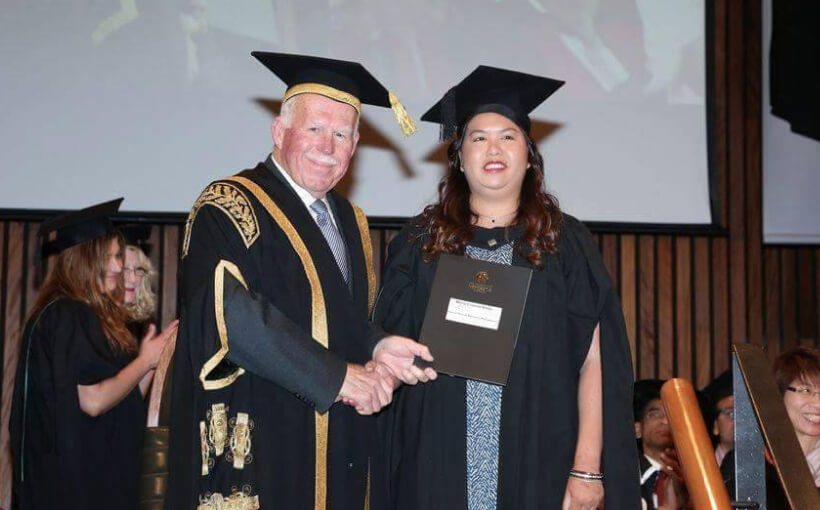 Krissy with the University Chancellor at her graduation ceremony. They are shaking hands and the Chancellor is holding up her diploma.