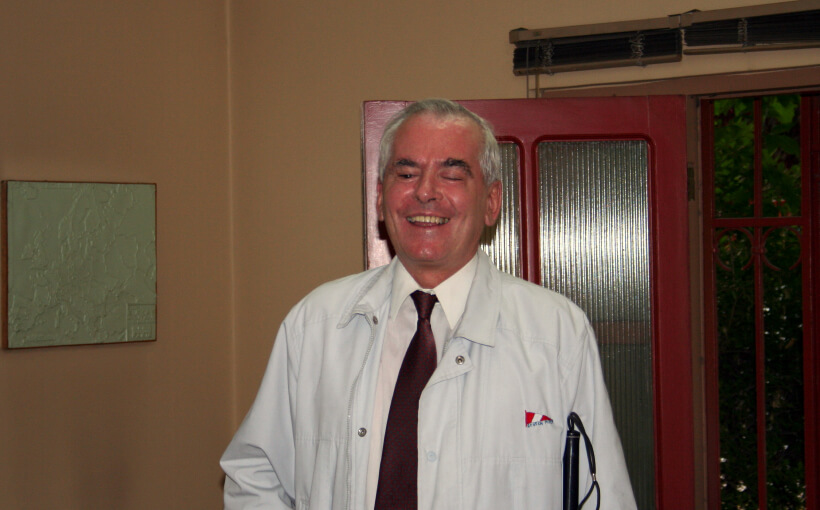 Fernando smiling to the camera, while posing with his white cane. He's wearing a white jacket and a white shirt with a maroon tie.