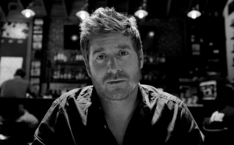 A black and white photo of Jon. He's sitting in a bar wearing a dark shirt.
