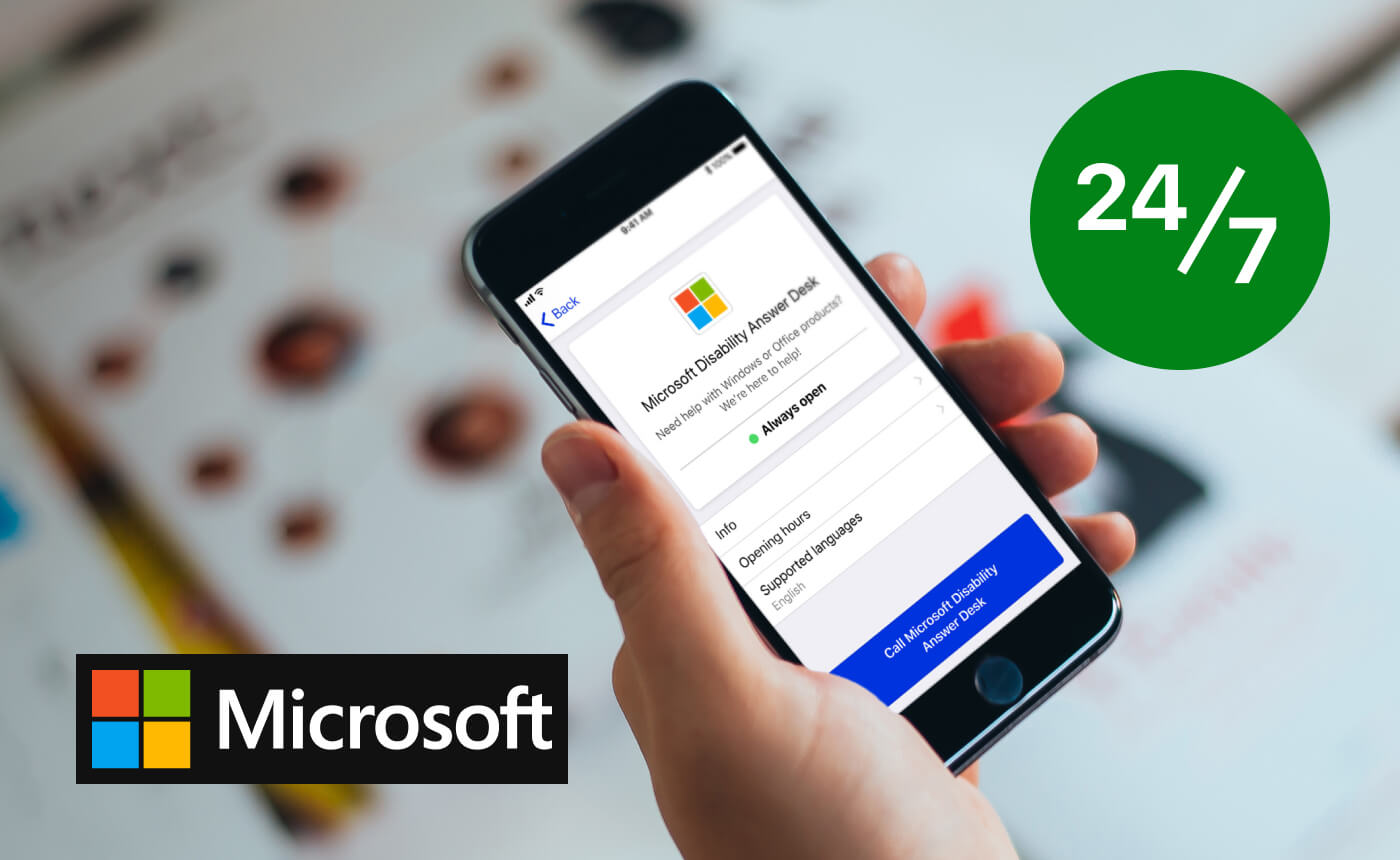 A hand-held iPhone depicts Microsoft's company page in the Specialized Help menu of the Be My Eyes app. The opening hours read 'Always open'. The bottom left corner of the image features the Microsoft logo and name. The upper right corner displays an icon saying '24/7'.