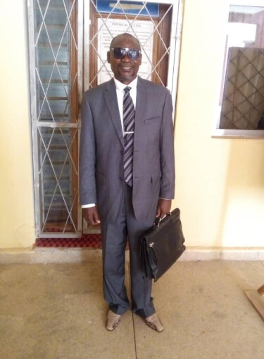 Godwin smiling to the camera. He's wearing suit and sunglasses and is holding a black briefcase.