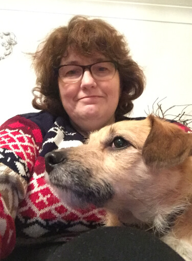Sally poses with her dog. She's wearing a knitted christmas sweater with reindeers.