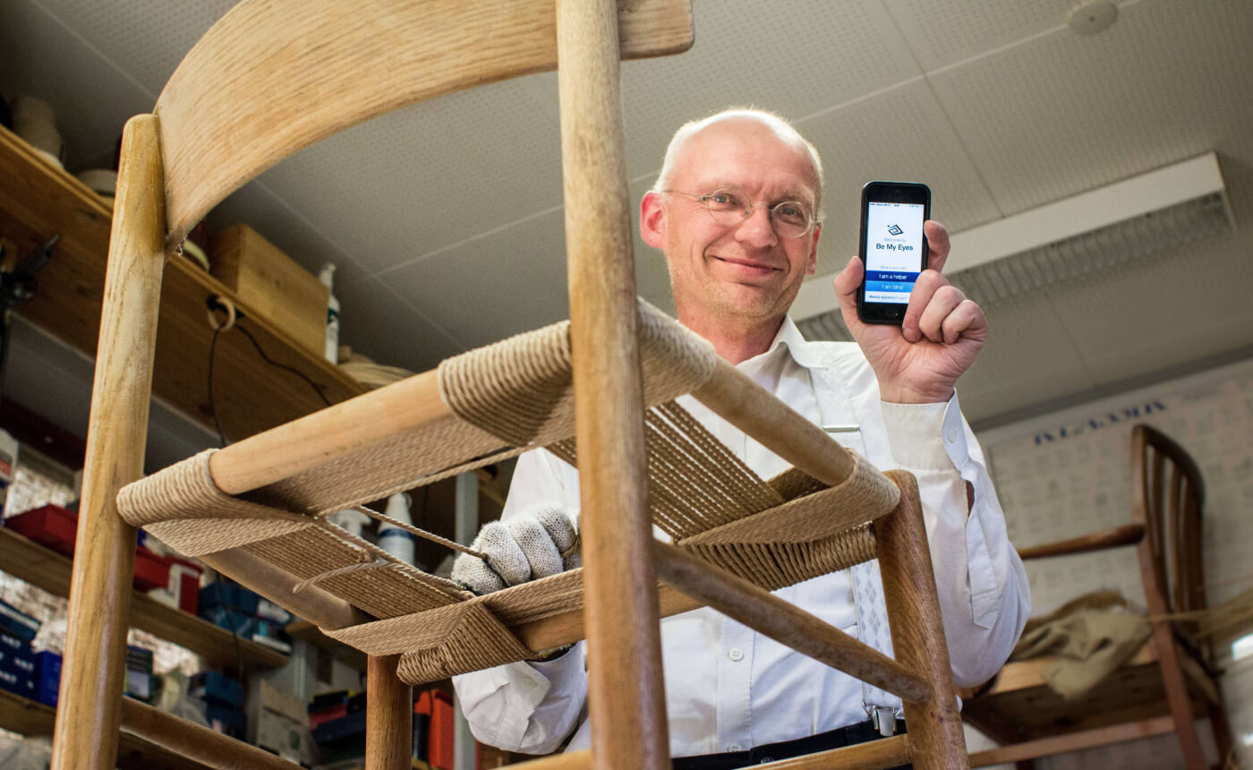 The Be My Eyes app was released for iOS on January 15th 2015. Be My Eyes founder, Hans Jørgen Wiberg, holding up an iPhone with the first version of the Be My Eyes app open while working on a chair.