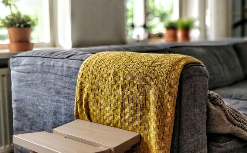 A yellow blanket folded over the armrest of a grey couch.