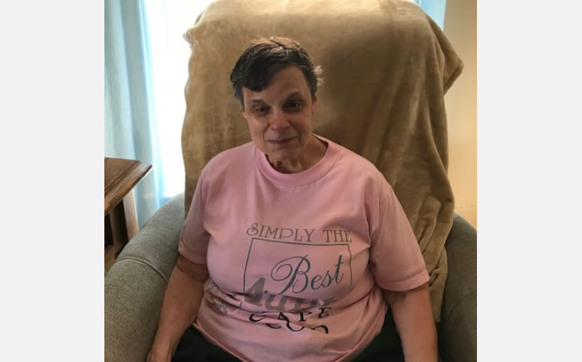 Diane sitting in a lounge chair. She's wearing a pink t-shirt and is smiling at the camera.