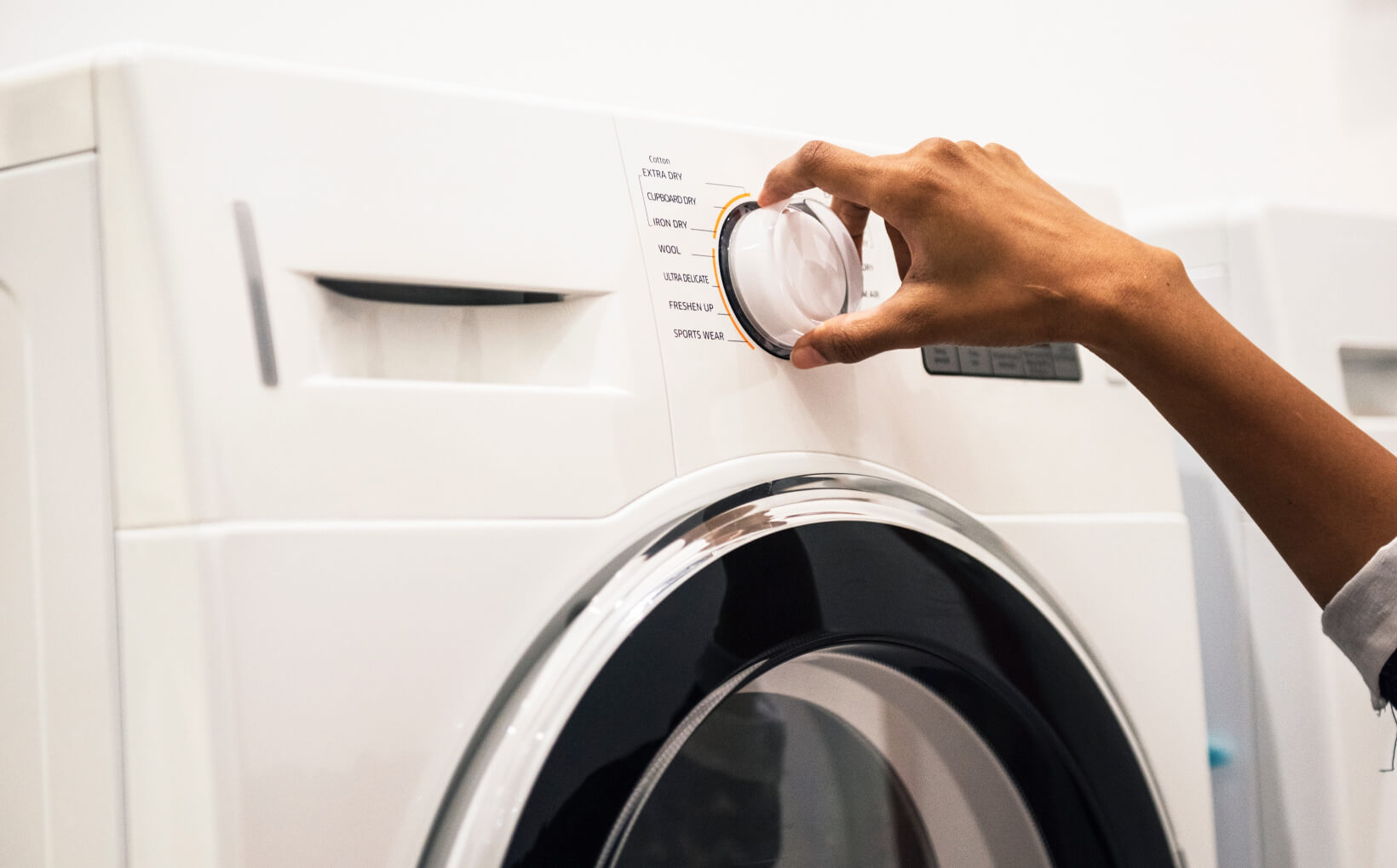 Hand turning the knob on a washing machine