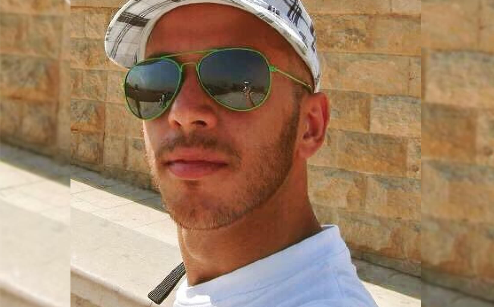 Closeup picture of Riccardo posing for the camera. He's outside in the sunshine and is wearing big green sunglasses and a white and black cap.