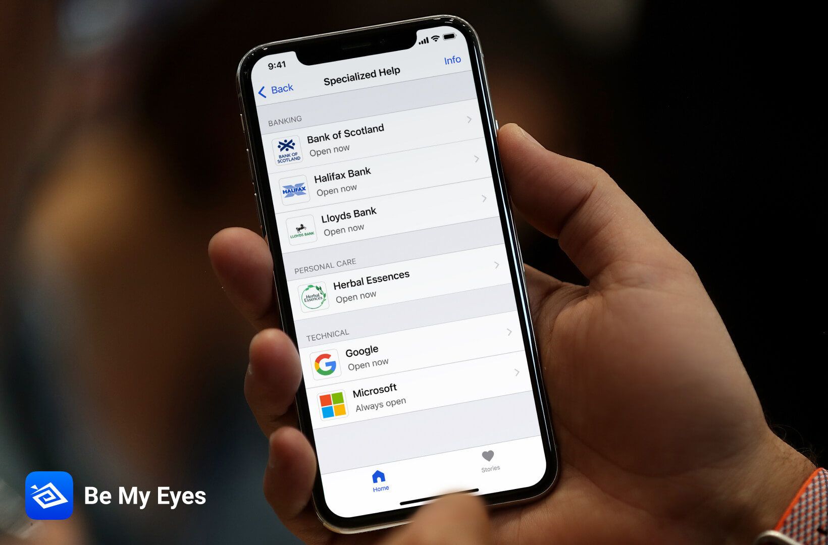 A phone screen displays a list of companies providing Be My Eyes support, including Google, Herbal Essences, Lloyds Banking Group and Microsoft.