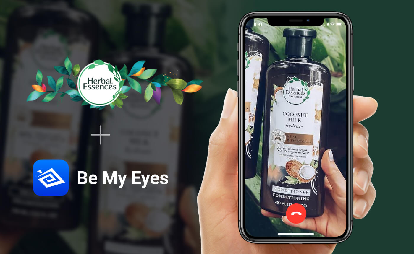 Hand holding phone. On the screen is an ongoing Be My Eyes call concerned with an Herbal Essences Coconut Milk conditioner. The image features the logos of Herbal Essences and Be My Eyes.
