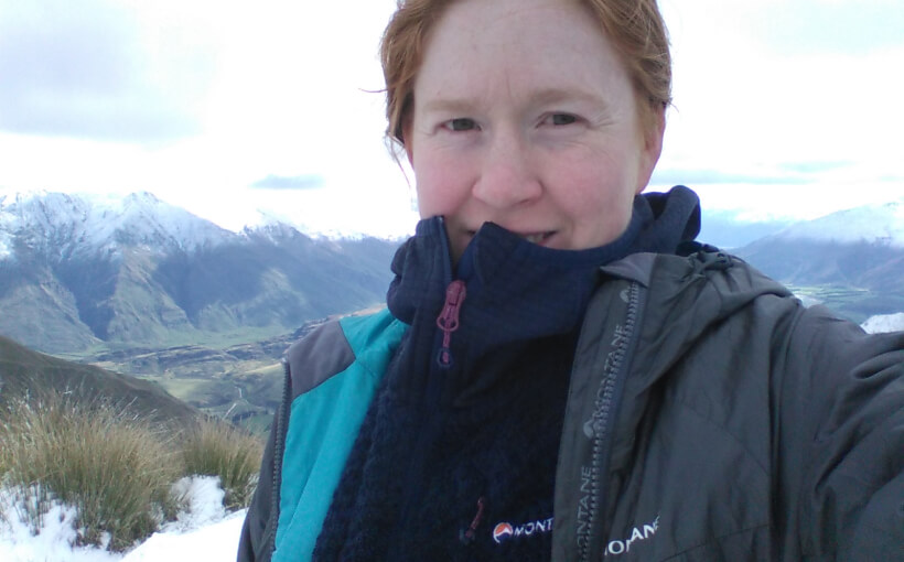 Jennie taking a selfie standing in the mountains. Behind her you can see mountains with snow on the top.
