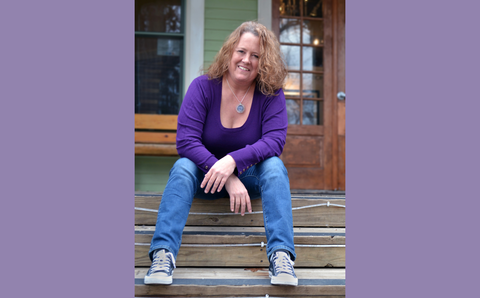 Jennifer sitting on the steps if her porch, smiling to the camera. She's wearing a purple top, blue jeans, Converse, and a necklace of her own design.