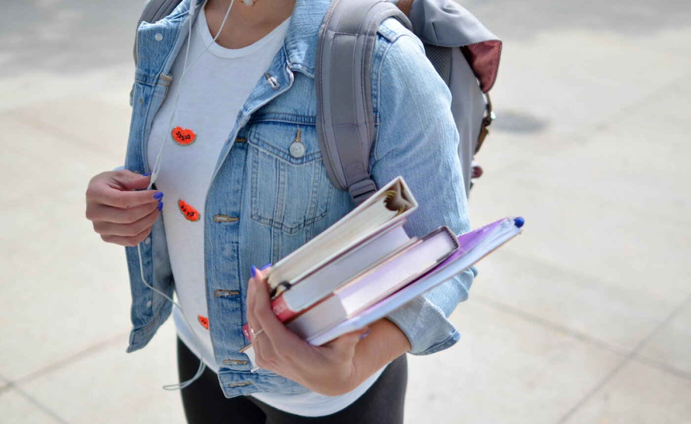 Female student walking with books in her hand and a backpack on.
