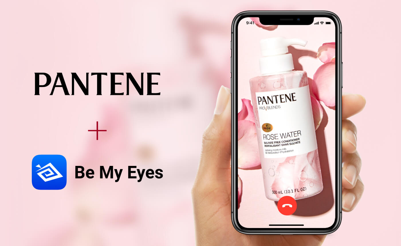 "Hand holding smartphone in a Be My Eyes call. The camera is pointed at a Pantene Rose Water conditioner. Text: ""Pantene + Be My Eyes"" on a light pink background."