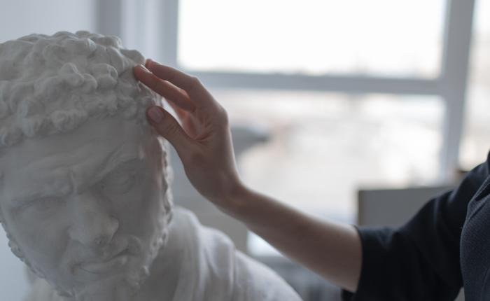Hand touching a sculpture.