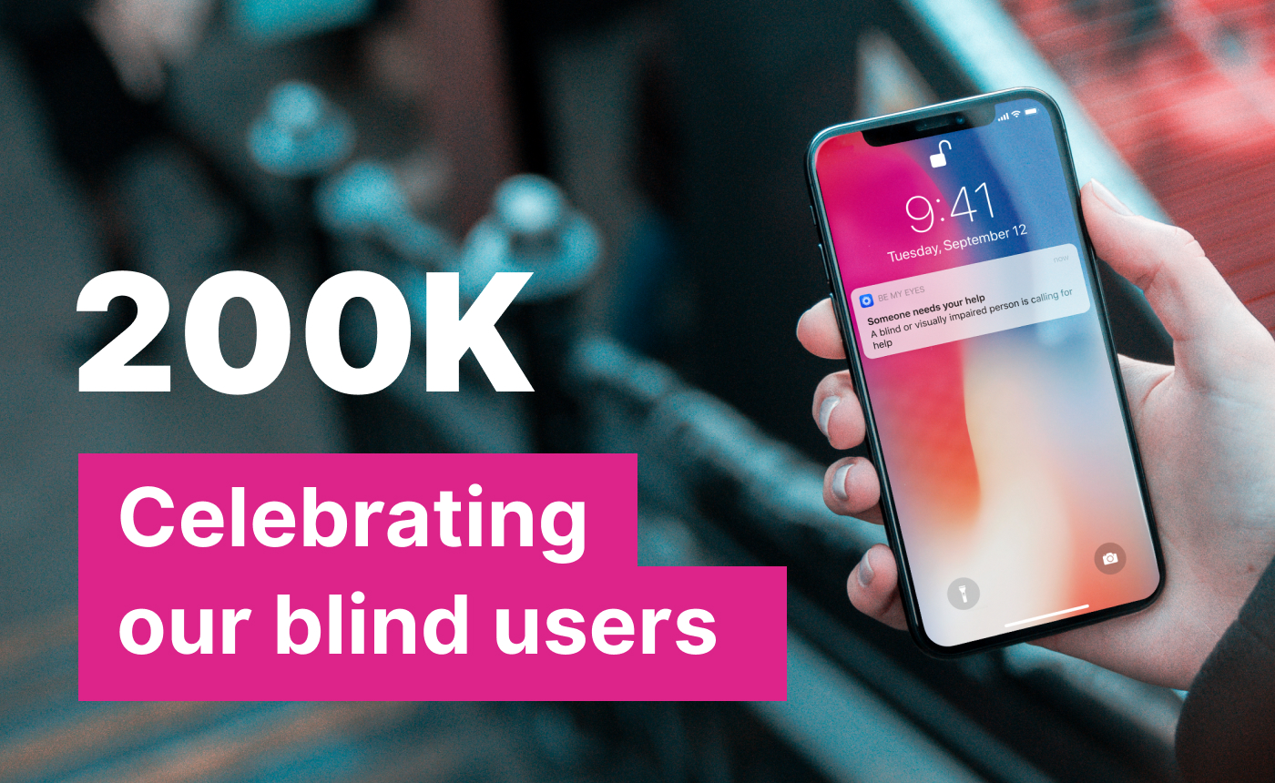 "Hand holding smartphone with a Be My Eyes notification on the screen. Text reads: ""200K - Celebrating our blind users"""