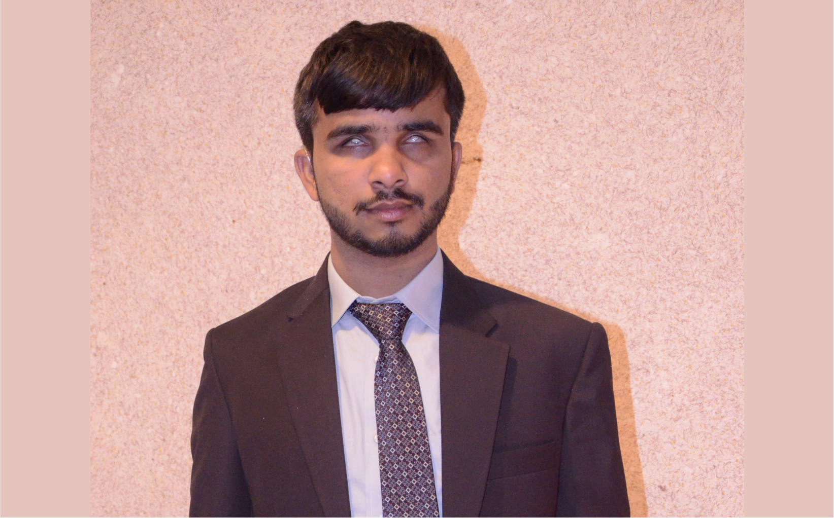 Abdullah posing for the camera wearing a suit and tie.
