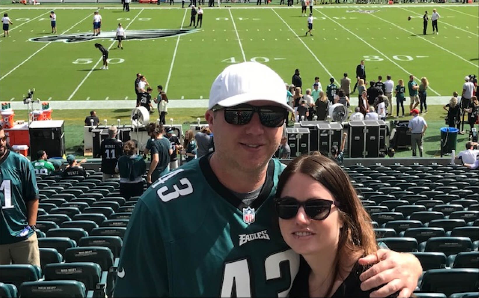 Bryan at the Philadelphia Eagles' football stadium with his wife, Jenna. Bryan is wearing an Eagles jersey, a cap and sunglasses.