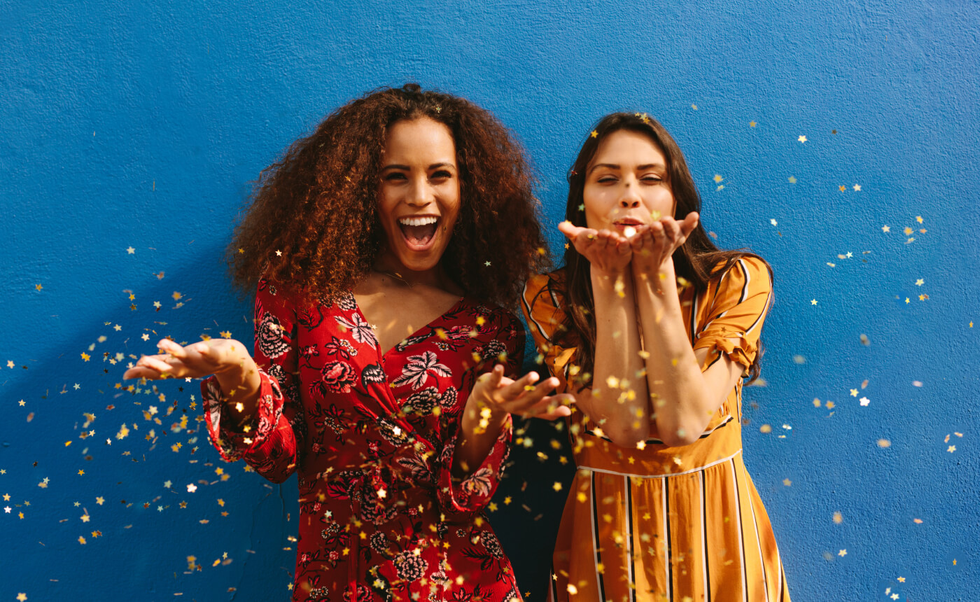 Two women celebrating by blowing and throwing gold confetti stars.