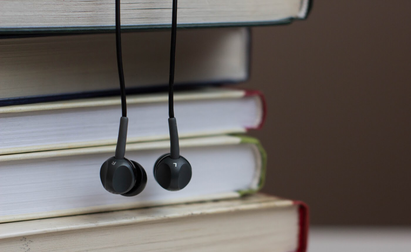 A pair of headphones dangles from a stack of books.