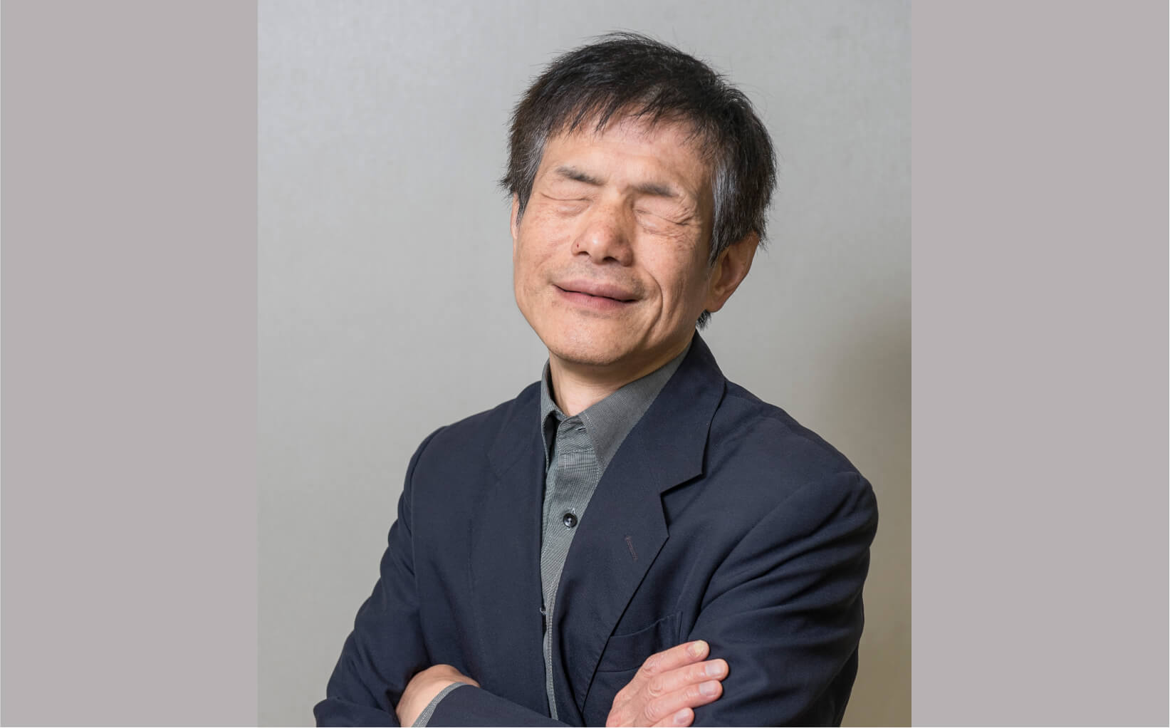 Chong Chan Yau posing with his arms crossed, wearing a shirt and a suit jacket.