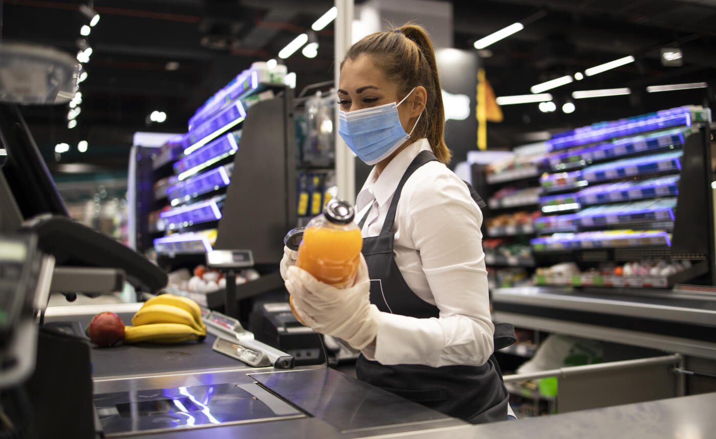 Supermarket cashier scanning items while wearing face mask and gloves.