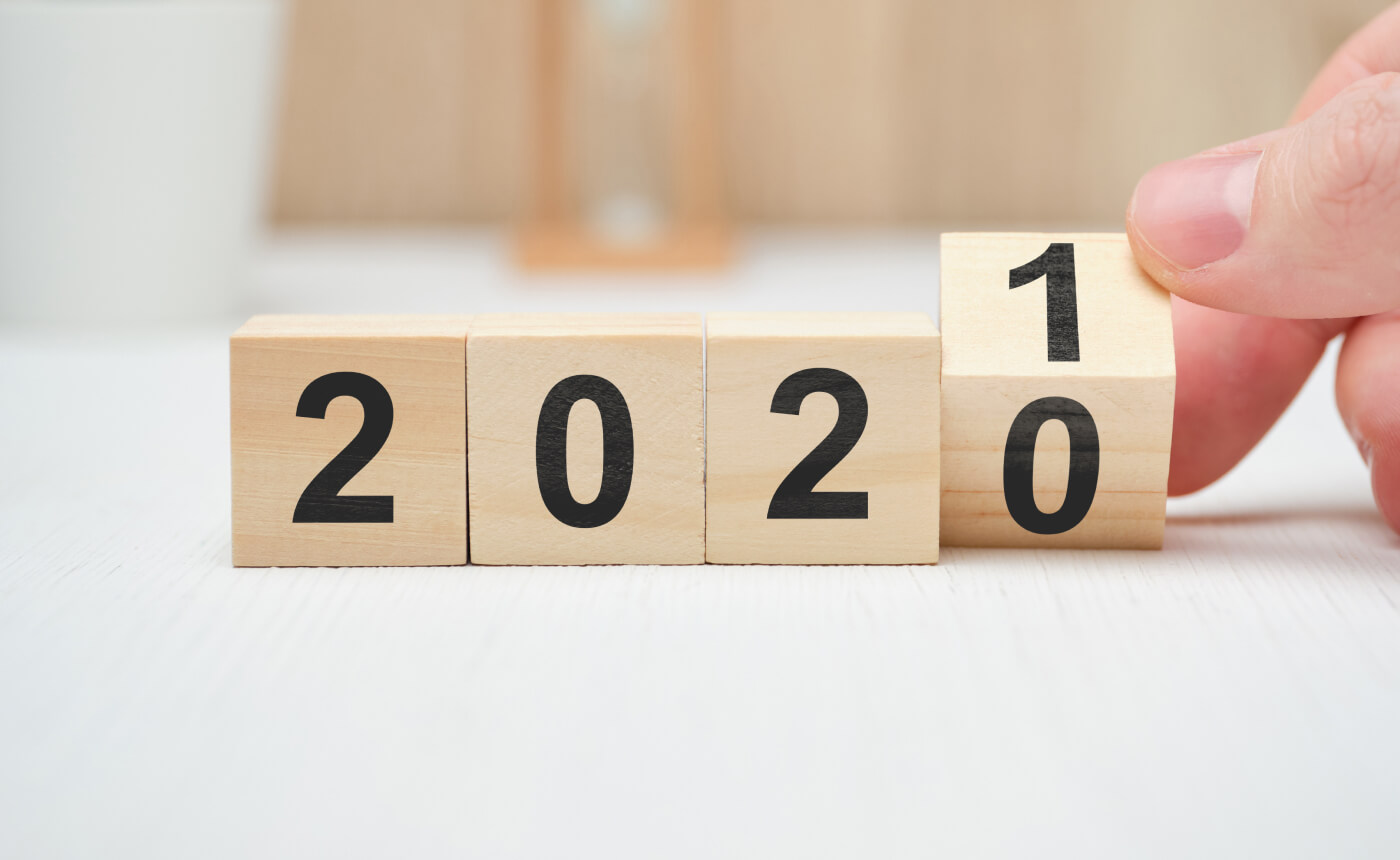 Four wooden blocks with numbers showing 2020. A hand is turning the last block from 0 to 1.
