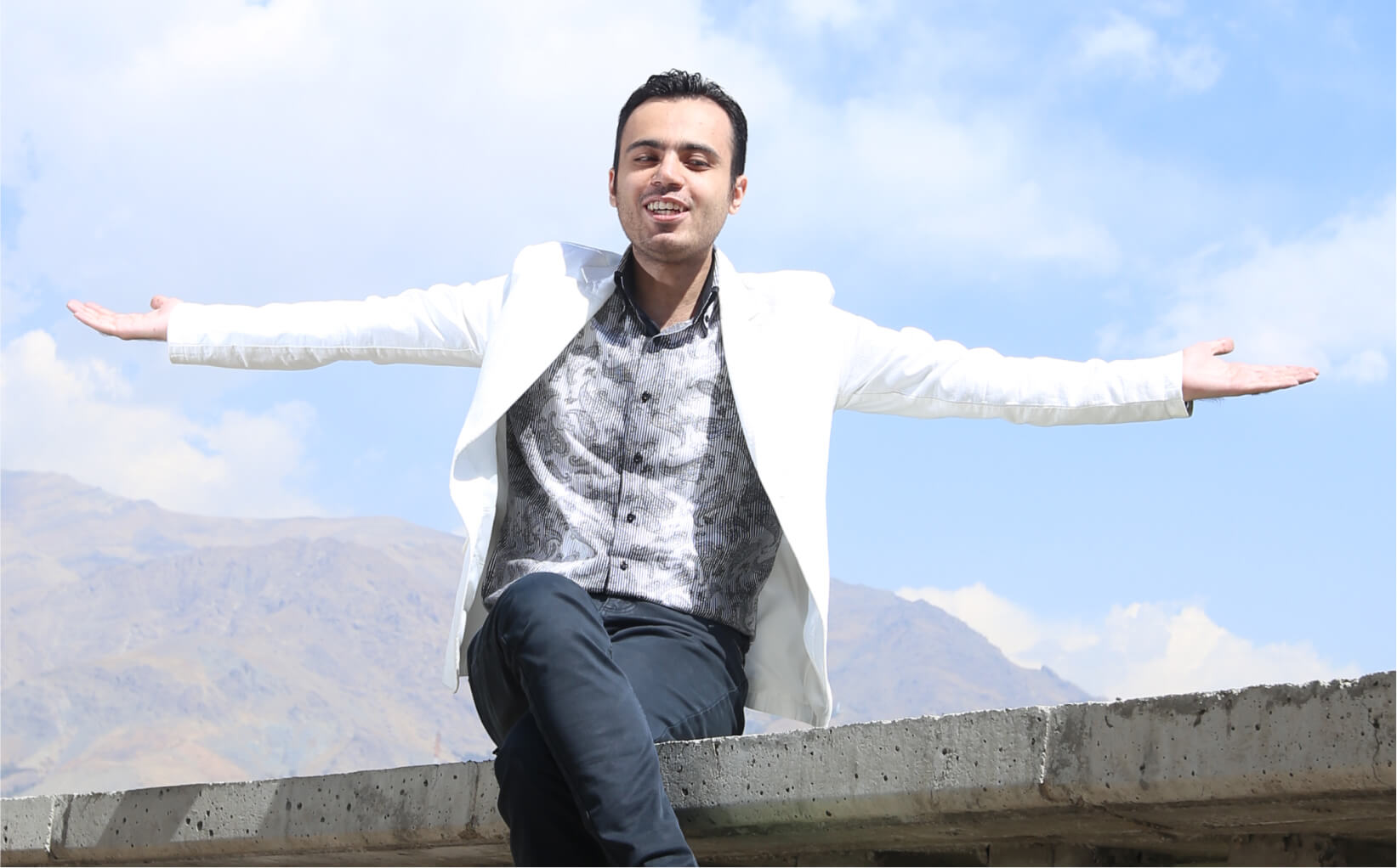 Parham sitting on a concrete wall holding his arms out with mountains in the background. He's wearing a white blazer jacket, a grey patterned shirt and black jeans.
