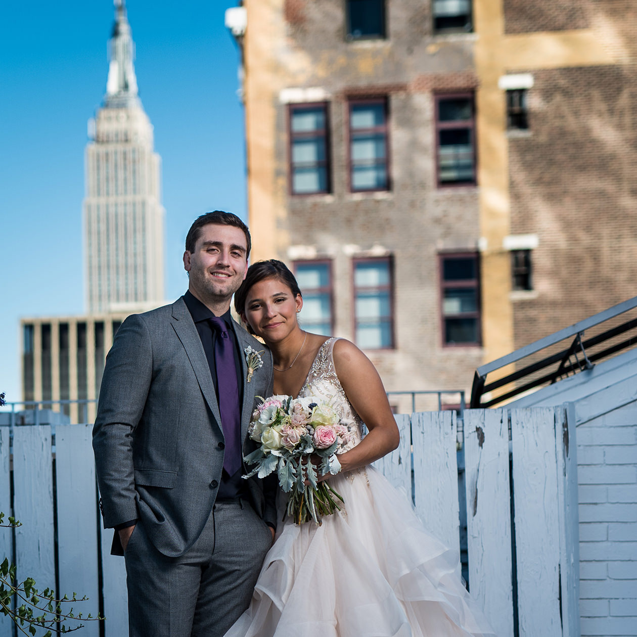 bride and groom standing in front of the Empire State Building