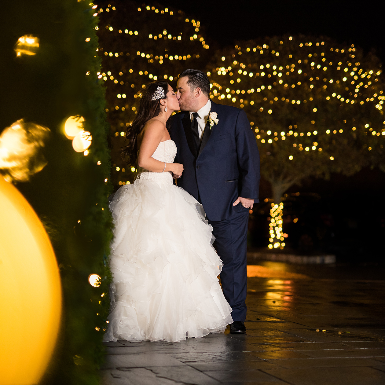 Bride and groom kissing in front of trees with string lights