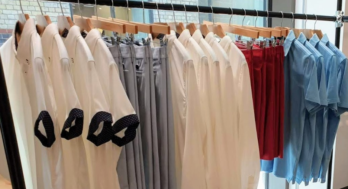 white and navy golf shirts, grey dress pants, white long sleeve dress shirt, red dress shorts and light blue polos hanging on a clothes rack in store.