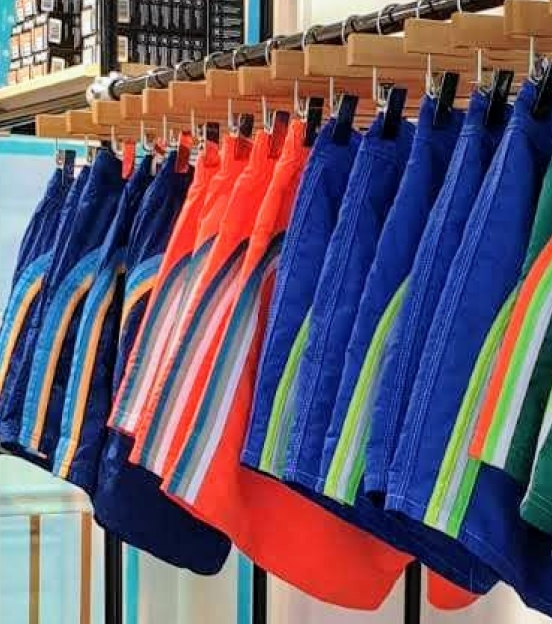 a bunch of colorful retro styled beach shorts hanging on a clothes rack in store.