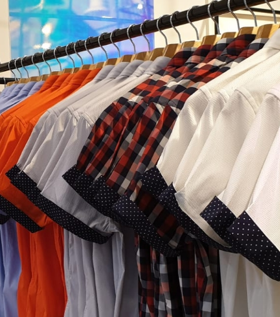 navy polka dotted cuffed short-sleeved dress shirts in various colors hanging on a clothes rack in store.
