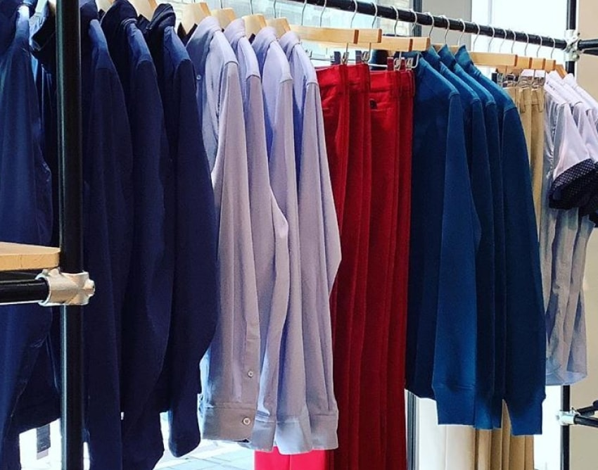 charles vane navy blue waterproof hooded jackets, light blue dress shirts, red dress pants, kaki dress pants hanging on a clothes rack